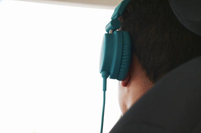 En grön hörlur som någon har på sig.