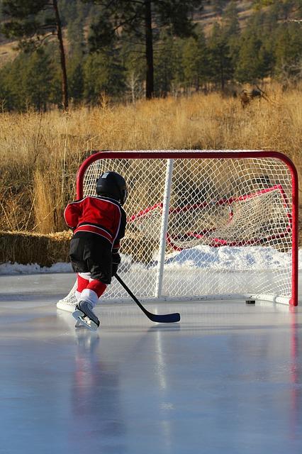 Ett barn som åker mot ett hockeymål och har skjutit in pucken i målet.