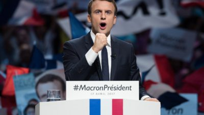 Macron står i en talarstol med knuten näve.