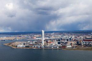 Utsikt över Malmö från luften ovanför vattnet. I mitten syns Turning Torso.