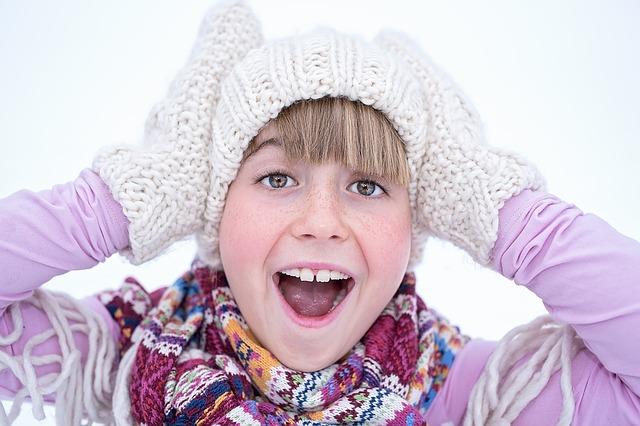 En flicka som ropar. Hon har vantar och mössa på sig och håller för öronen.