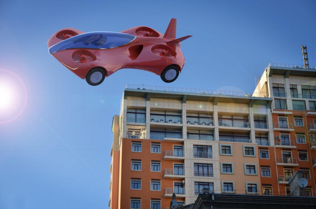 Röd bil som flyger över ett hus.