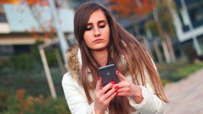 En kvinna med vit jacka och långt brunt hår håller i och tittar på sin smartphone.