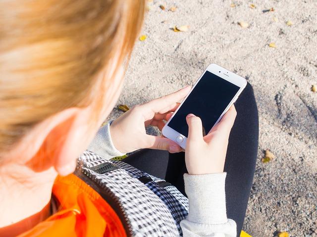 Bild på person snett uppifrån som håller i en smartphone. Man kan inte se ansiktet på personen.