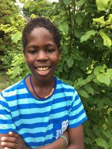 Andrew ler i sin blårandiga tröja framför en grön buske.