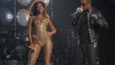 Jay-Z står till höger och sjunger i en mikrofon samtidigt som han tittar på Beyoncé. Beyoncé står till vänster och tittar ut mot publiken och ser glad ut.