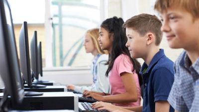 Tre elever sitter på rad och skriver på datorer.