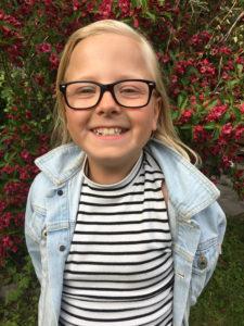 Felicia ler stort i sina glasögon framför rosa blommor.