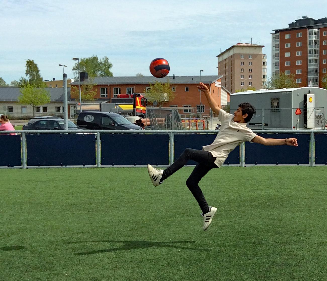 En pojke på en fotbollsplan ska precis göra en cykelspark.