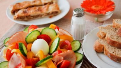 En stor frukost med ägg, grönsakger och bröd fint upplagt på ett ljust bord.