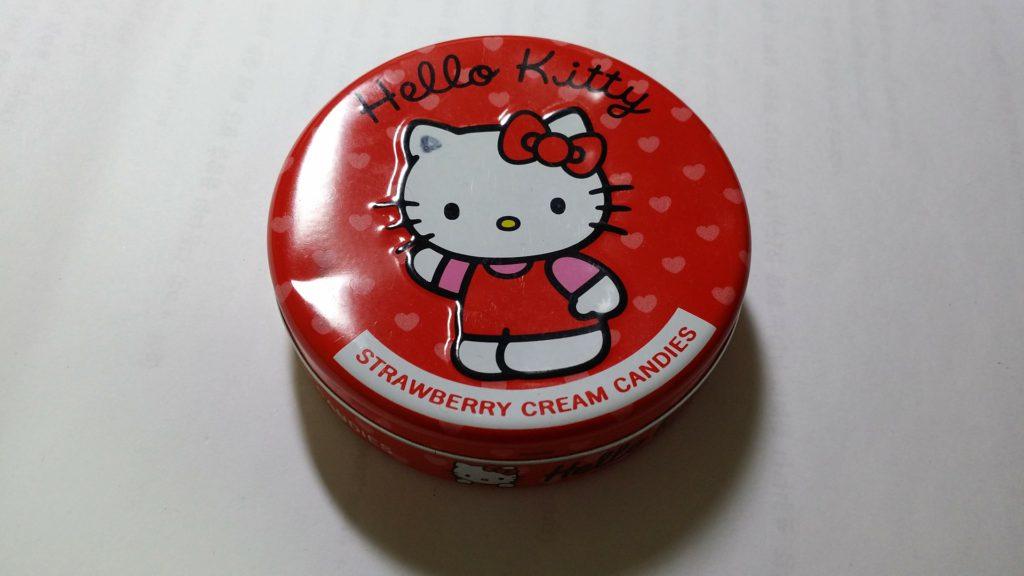 En röd godisask med Hello Kitty på som vinkar med ena tassen.