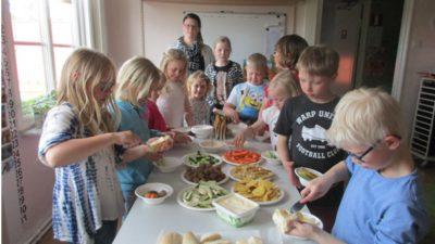 Massor med barn runt ett bord fyllt med bröd och pålägg.