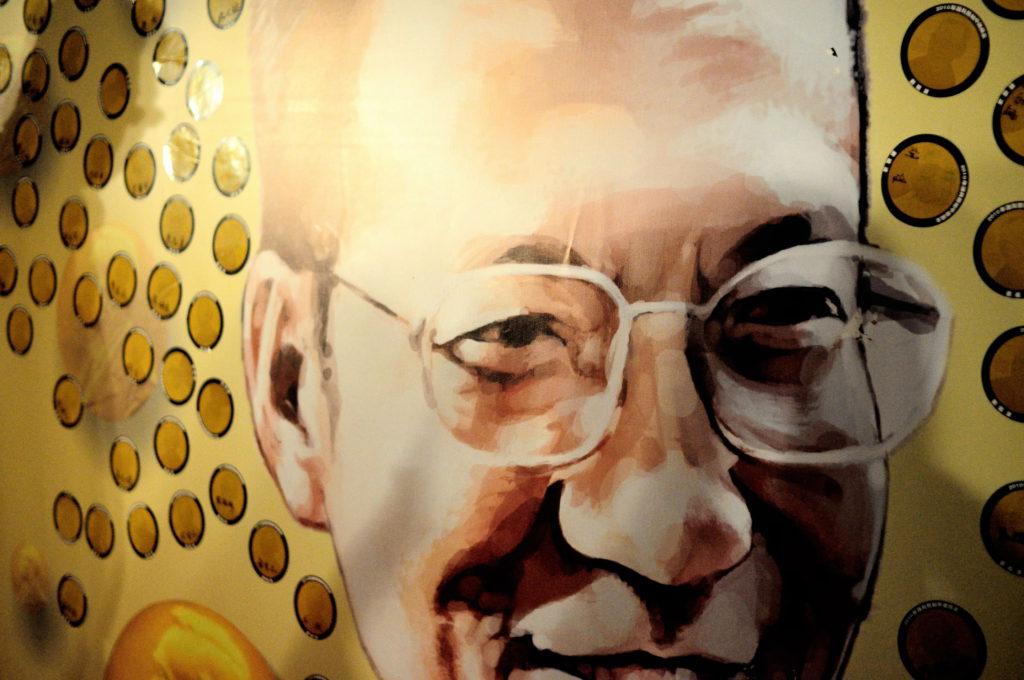 Liu Xiaobo ler ett snett leende och hans glasögon utan bågar lyser i det starka ljuset från sidan.