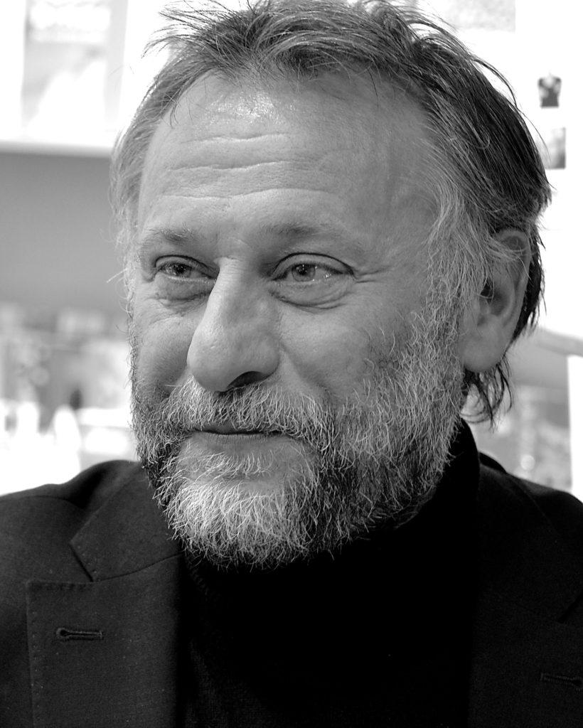 En svartvitMichael Nyqvist ler svagt.