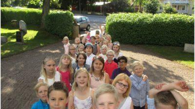 Många barn står i en rad på grusväg. De har sommriga kläder på sig. I bakgrunden syns gröna buskar och ett träd.