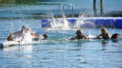 Några barn som plaskar och badar i en sjö.