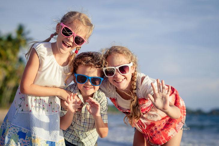 Tre syskon i solglasögon med olika färger ler framför havet.