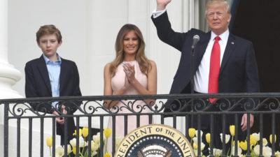 Donald Trum står på vita husets balkong och vingar med en hand. Bredvid honom står Melania som klappar händerna. Bredvid Trump och Melania står deras son.