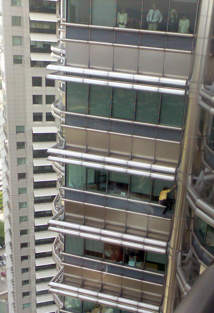 En man i gul tröja klättrar på en hög byggnad.