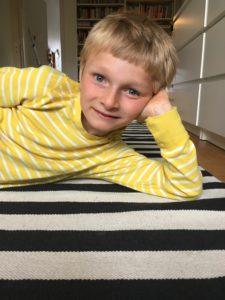 Arvid ligger på en randig matta.