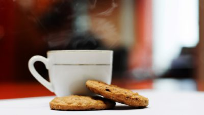 En rykande kopp kaffe och två kakor.