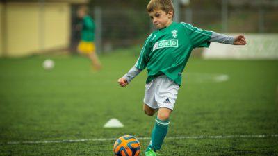 En kille i grön tröja sparkar på en fotboll.