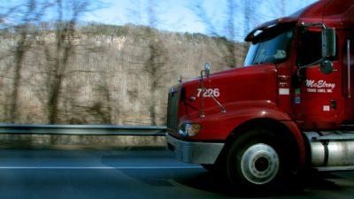 En stor röd lastbil kommer inkörande från höger.