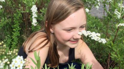 En flicka sitter leende i höga blommor.