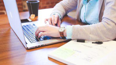 En students händer knapprar på datorn framför hen. Bredvid datorn står en kopp med te och på andra sidan datorn ligger en bok uppslagen.