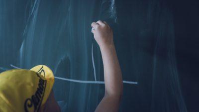 Ett barn i gul keps skriver med en vit krita på en svart griffeltavla.