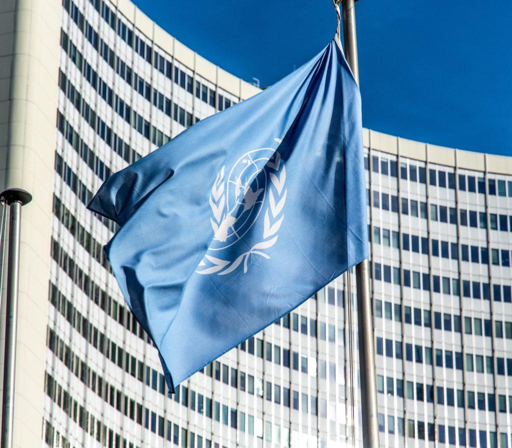 En blå flagga med FN:s symbol på. Flaggan hänger på en flaggstång framför en skyskrapa.