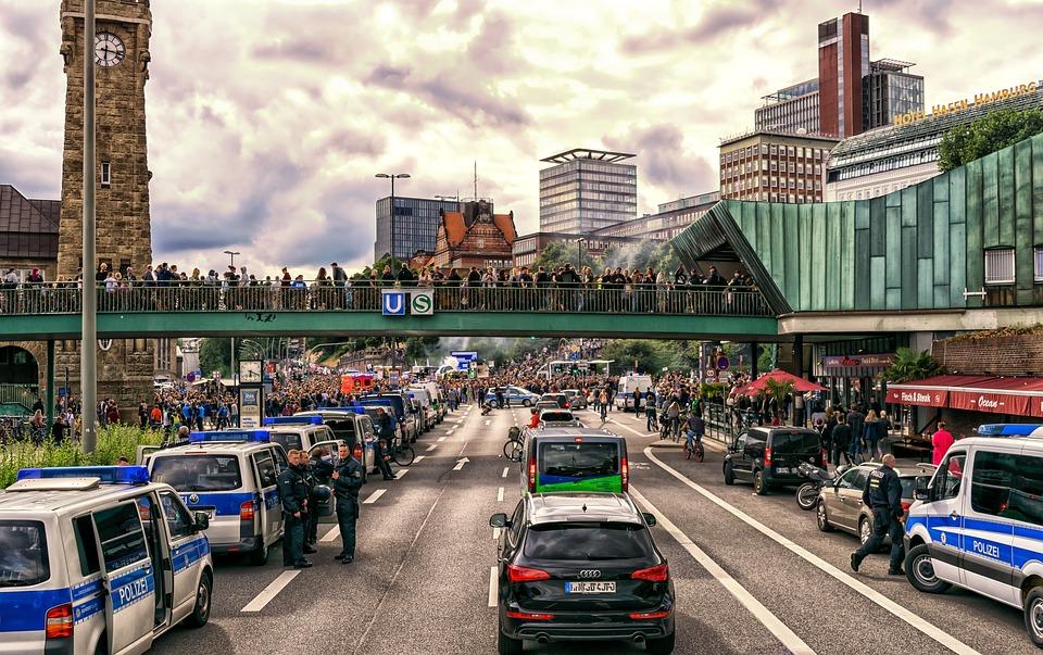 Väg i Hamburg med många polisbilar. Längre bort på vägen är det många människor som protesterar.