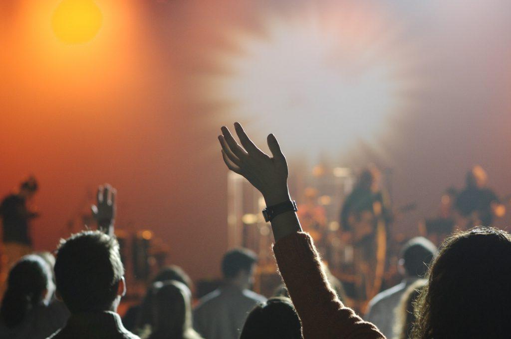 En hand sträcks upp för att hylla artisterna som står på scen.