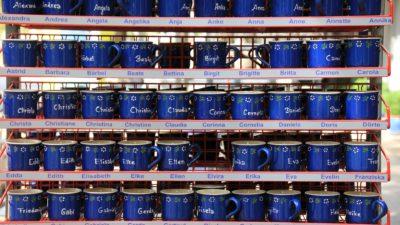 många blåa muggar med olika namn på.