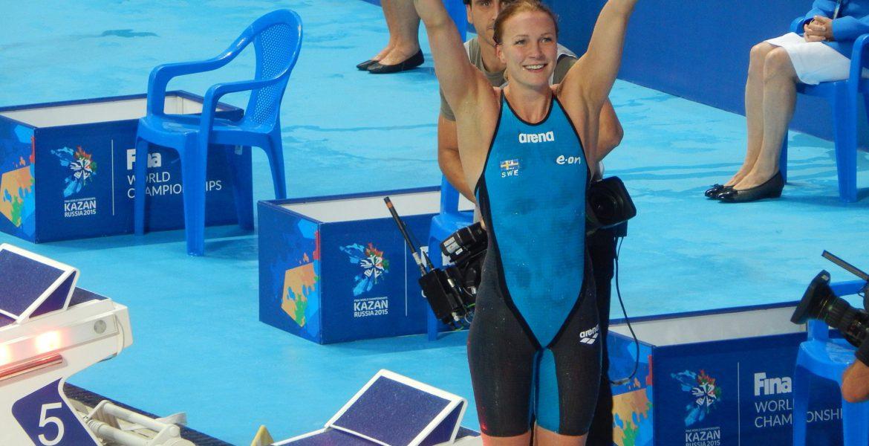Sarah sträcker upp händerna över huvudet.