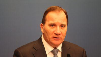 Stefan Löfven står och pratar med en mikrofon framför sig. Han har kavaj, skjorta och slips. Han har tunt brunt hår, små ögon och en stor näsa.