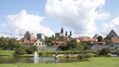 Staden Visby med hus och kyrktorn. Framför staden är en sjö med en liten fontän i.