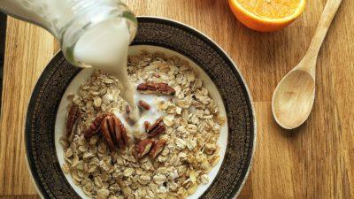 Tallrik med havregryn. Mjölk hälls i tallriken. Bredvid ligger apelsinhalvor.