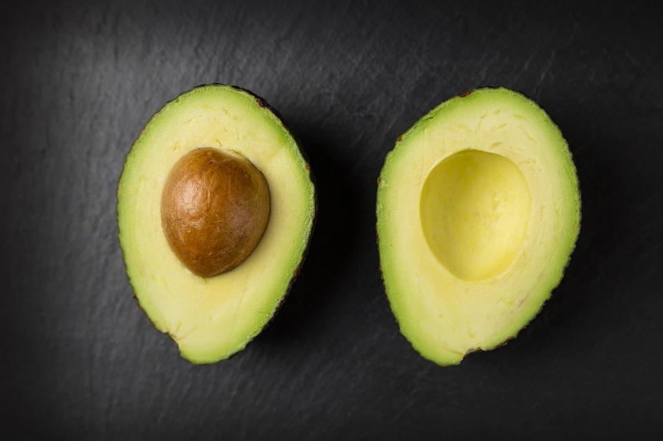 En uppdelad avokado. Ena halvan har kärnan kvar.