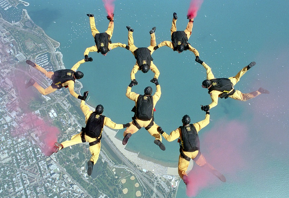 Åtta fallskärmshoppare gör en formation i luften som ser ut som två ringar som går in i varnadra.