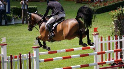 En man sitter på en häst som hoppar över ett randigt hinder.