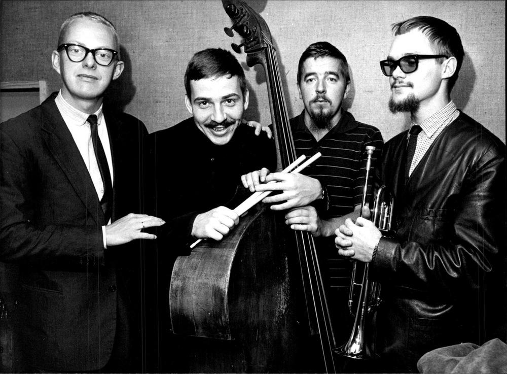 Fyra musiker står på rad med sina instrument. Den andra från vänster är Janne Carlsson.