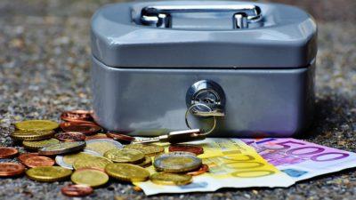 Två sedlar och massa mynt ligger framför ett kassaskrin.