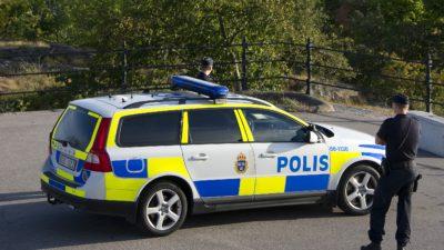 Två poliser står vid en polisbil.