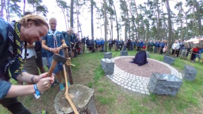 Scouter står i en ring och tittar på när Scouternas ordförande hugger av ett rep med en yxa.