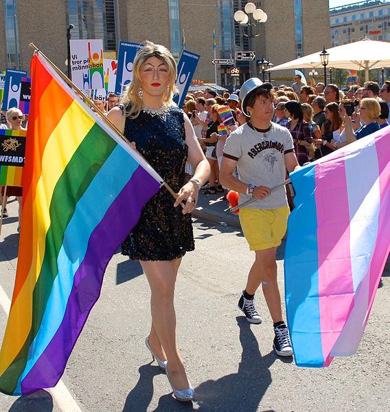 Två personer går med varsin flagga. Den ena flaggan har regnbågens färger. Den andra är transflaggan som är blå rosa och vit.