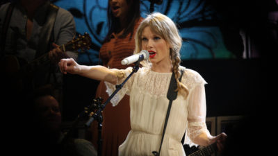 Taylor Swift står på scenen och sjunger.