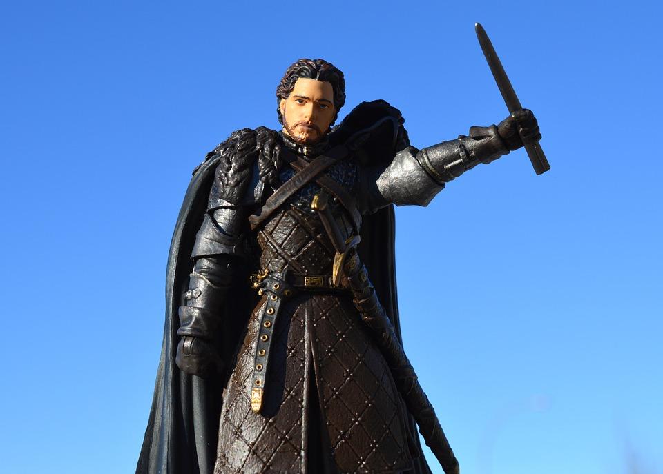 En karaktär från Game of thrones står med höjt svärd och ser bestämd ut.