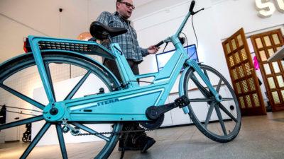 En man står bakom en blå cykel i plast.