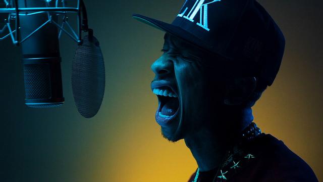 En person med keps som sjunger in i en studiomikrofon.